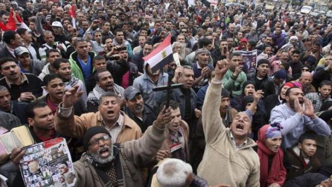 Un manifestante (i) sostiene una cruz y un ejemplar del Corán, durante la manifestación convocada en la Plaza Tahrir, en El Cairo, Egipto.