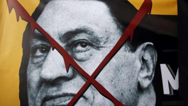 Manifestantes en Estambul portal una pancarta con la cara del presidente egipcio, Mubarak.