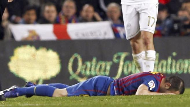 El centrocampista del FC Barcelona Andrés Iniesta (abajo) permanece en el suelo en presencia de Arbeloa.