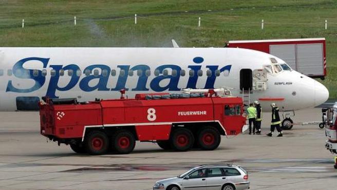 Fotografía del 20 de agosto de 2004 de bomberos examinando un avión de pasajeros de la aerolínea española Spanair en el aeropuerto de Colonia (Alemania). Spanair confirmó la suspensión de operaciones a partir del viernes 27 de enero de 2012, lo que ha supuesto la cancelación de todos sus vuelos.