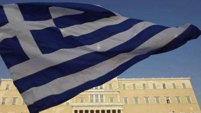 Imagen de archivo de una bandera griega, con el Parlamento del país al fondo.
