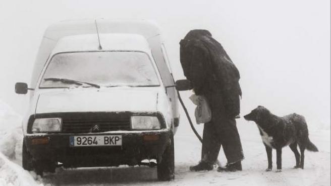 Una persona junto a su perro intenta abrir la puerta de su vehículo en Monreal (Navarra).