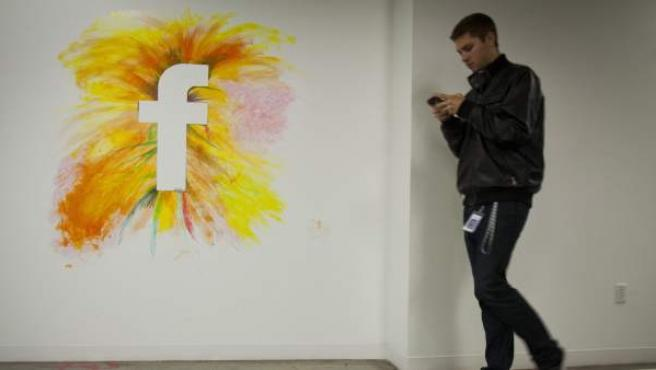 Un empleado camina por un muro con el logo de la red social Facebook en la sede de la compañía en Menlo Park, California.