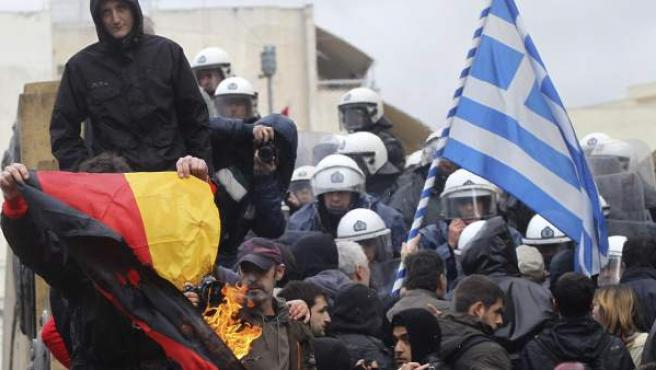Un manifestante quema una bandera de Alemania mientras otros tratan de irrumpir en el Parlamento griego en Atenas.