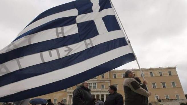 Un manifestante sostiene una bandera de Grecia frente al Parlamento griego en Atenas.