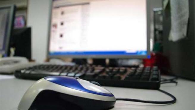 Imagen de un ordenador con el ratón en primer plano.