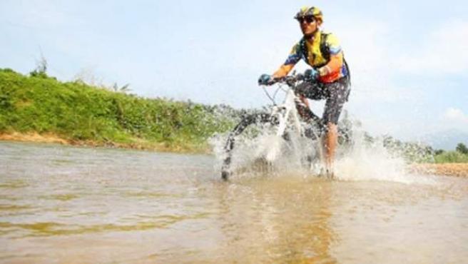 Un hombre avanza sobre el agua sobre su bicicleta de montaña.