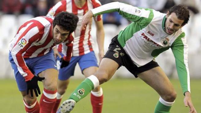 Christian Stuani y Arda Turan pelean por un balón en el Racing - Atlético.