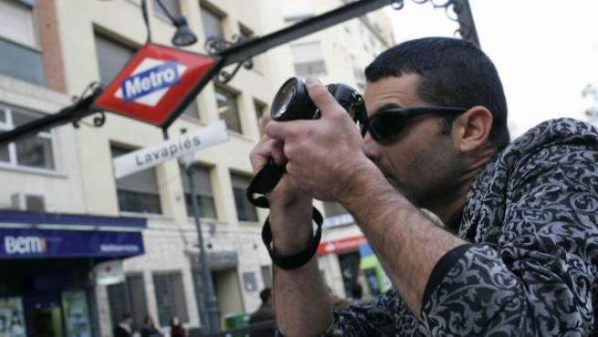 Un hombre fotografía la plaza de Lavapiés junto a la salida de la boca de Metro.