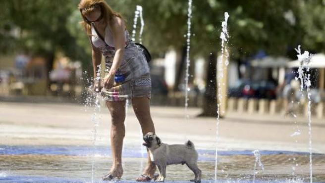 Una mujer pasea a su perro por una fuente de agua.