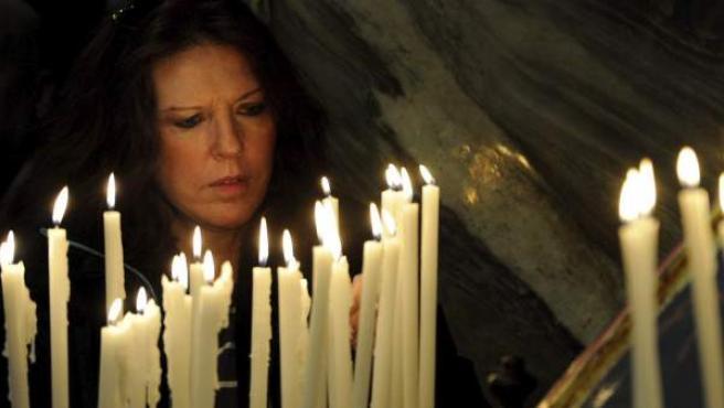 Una mujer enciende una vela durante la comida navideña celebrada en la monumental basílica romana de Santa María in Trastevere.