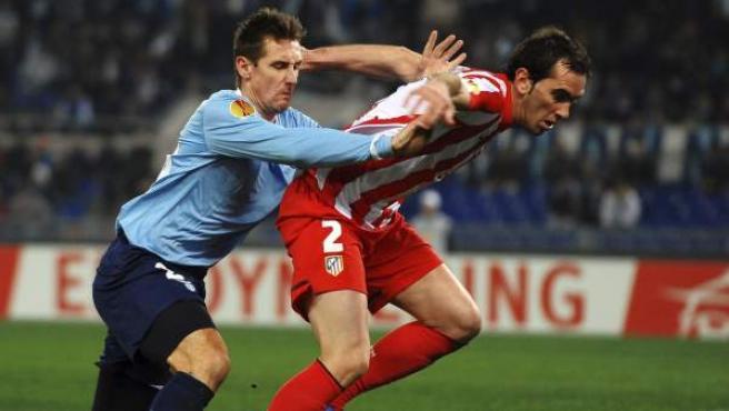 Miroslav Klose y Diego Godín luchan por el balón en un Lazio - Atlético de Madrid.