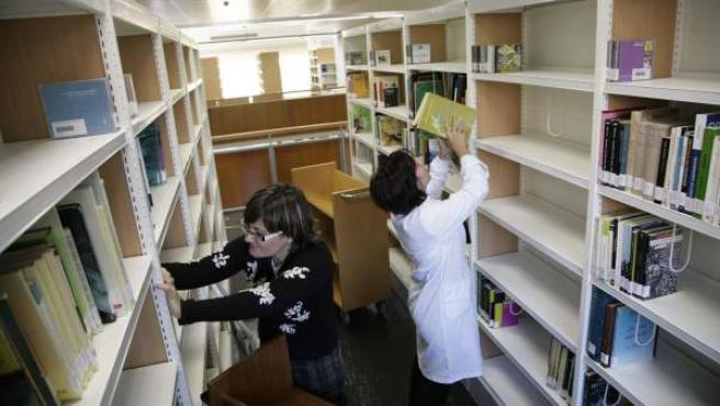 Dos trabajadoras colocan las estanterías de una biblioteca.