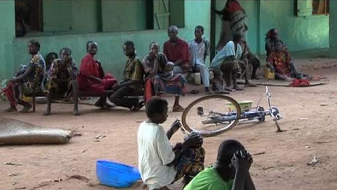 Varias personas esperan cerca de un centro de MSF donde se trata la malaria.