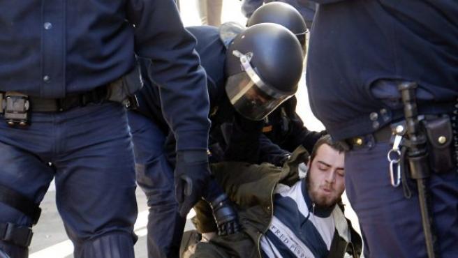 La policia custodia a un detenido durante los incidentes entre estudiantes y policias en el centro de Valencia este lunes.