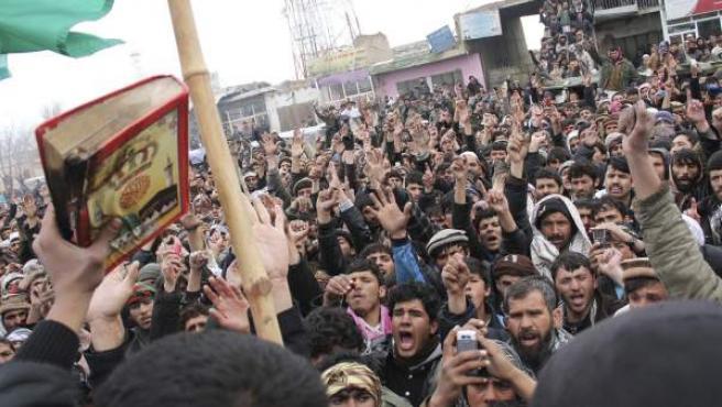 Un afgano muestra la copia del Corán que fue supuestamente quemada por soldados estadounidenses durante una protesta en Bagram (Afganistán).