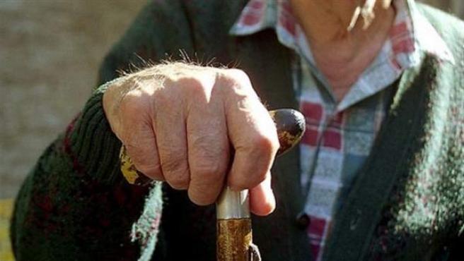 Un anciano apoyado en su bastón.