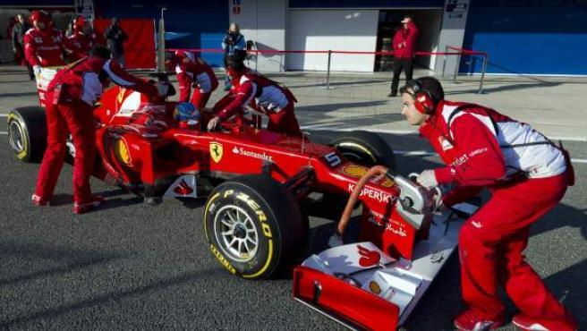 El piloto español Fernando Alonso al volante del Ferrari F2012, en 'boxes' con sus mecánicos.