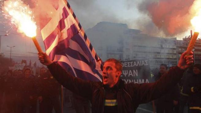 Policías, guardas costeros y bomberos se manifiestan este martes contra las medidas de austeridad del gobierno heleno, frente al parlamento griego en Atenas.