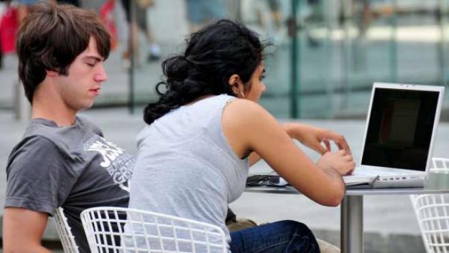 Dos jóvenes ante un ordenador portátil.