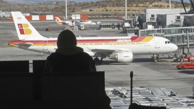 Un pasajero mira un avión de Iberia en la pista del aeropuerto de Barajas en Madrid.
