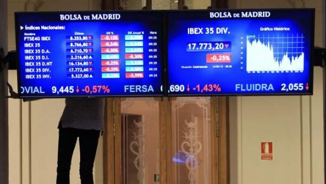 Dos operarios de la Bolsa de Madrid ponen a punto un panel de cotizaciones.