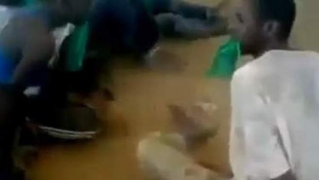 Prisioneros libios obligados a meterse en la boca la bandera del país.