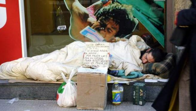 Un mendigo duerme próximo a un comercio.