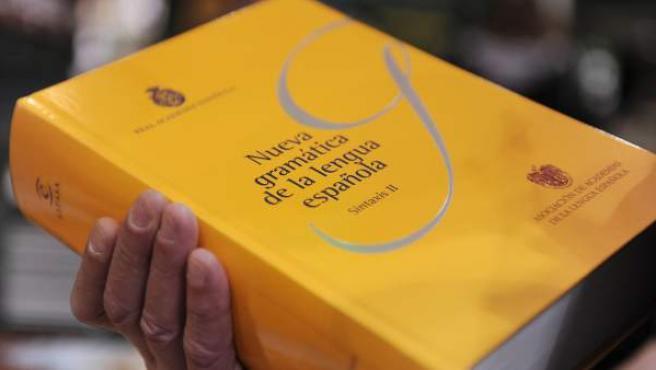 Una persona sostiene un libro de la Real Academia de la Lengua Española (RAE) sobre la 'Nueva gramática de la Lengua'.