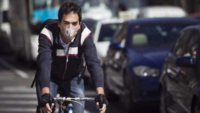 Imagen de un ciclista con una mascarilla circulando por las calles de Madrid.