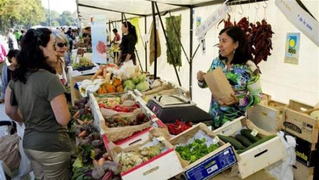 Una mujer vende productos agrícolas en un mercado de Aragón.