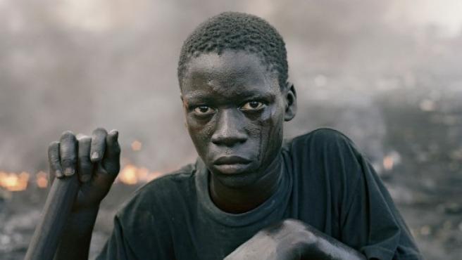 Uno de los chicos que trabajan en un vertedero de ordenadores en Ghana, buscando restos metálicos entre los aparatos incinerados