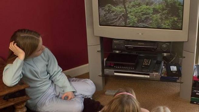 Un grupo de niñas ve la televisión.