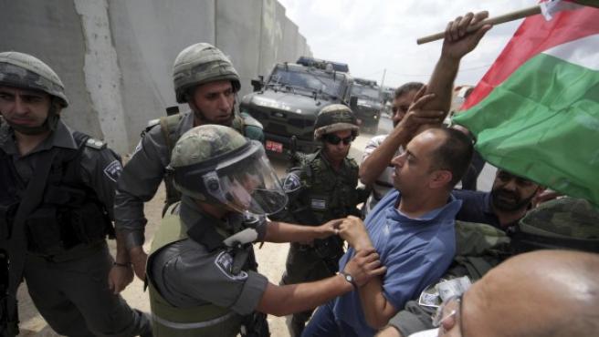 Soldados israelíes detienen a simpatizantes de Palestina.
