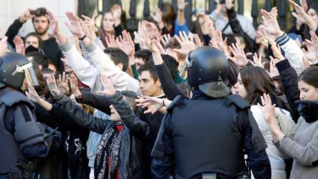 Estudiantes protestan antes los agentes antidisturbios en la plaza del Ayuntamiento de Valencia.