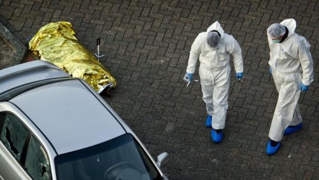Policías inspeccionan un coche aparcado junto al cadáver de una de las víctimas del tiroteo en el comercial de Alphen aan den Rijn.