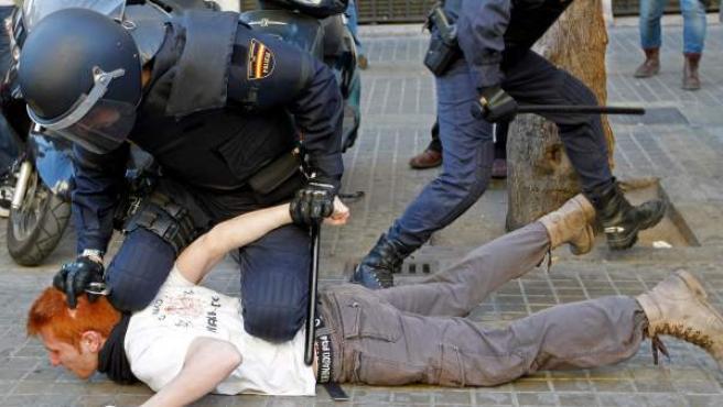 Un policía custodia a un detenido durante los incidentes entre estudiantes y policías en el centro de Valencia.