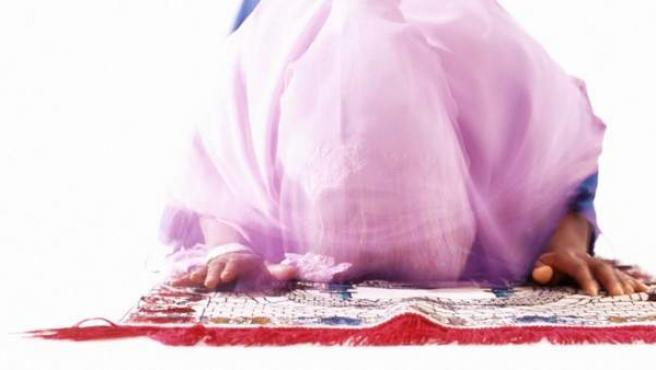 Una mujer vestida con hiyab (velo islámico) orando.