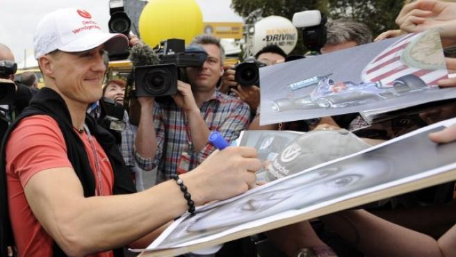 Michael Schumacher firma autógrafos a los aficionados.
