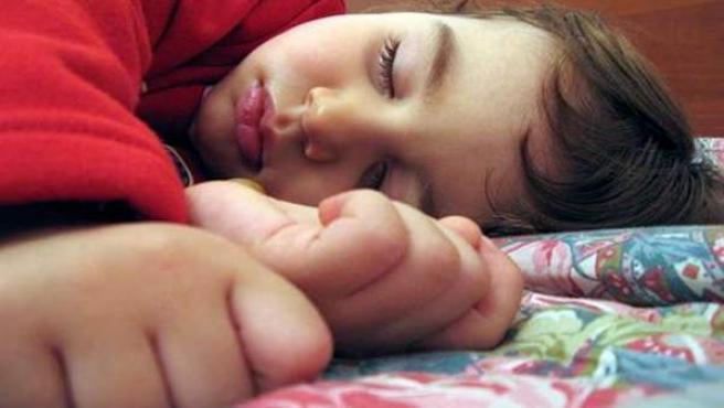 Un niño pequeño durmiendo sobre la cama.