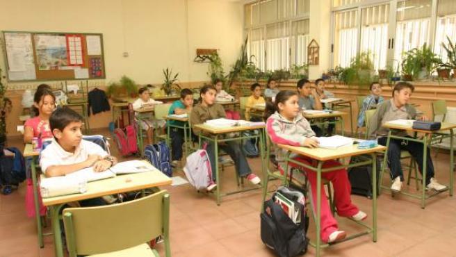 Los alumnos realizan sus tareas en la clase de un colegio.