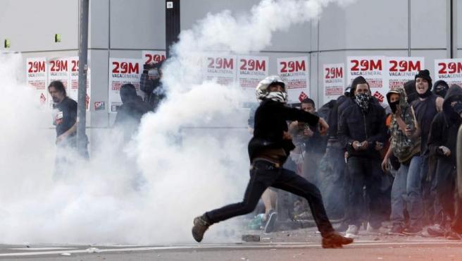 Manifestantes atacan a los mossos en Barcelona durante los disturbios ocurridos en la jornada de huelga general convocada por los sindicatos.