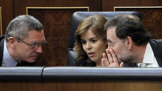 El presidente del Gobierno, Mariano Rajoy, conversa en el Congreso con la vicepresidenta, Soraya Sáenz de Santamaría, y el ministro de Justicia, Alberto Ruiz-Gallardón.
