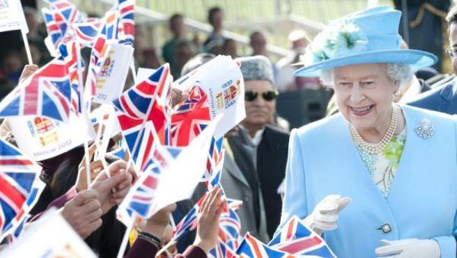 La reina Isabel II durante un acto saludando a un grupo de admiradores