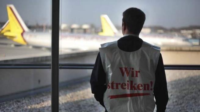 Un empleado de los servicios de tráfico en tierra observa la pista del aeropuerto Colonia/Bonn en Colonia, Alemania. La huelga temporal convocada por el sindicato gremial de servicios públicos Ver.di en los aeropuertos alemanes ha provocado la cancelación de centenares de vuelos sobre todo de las compañías locales Lufthansa y Air Berlín.