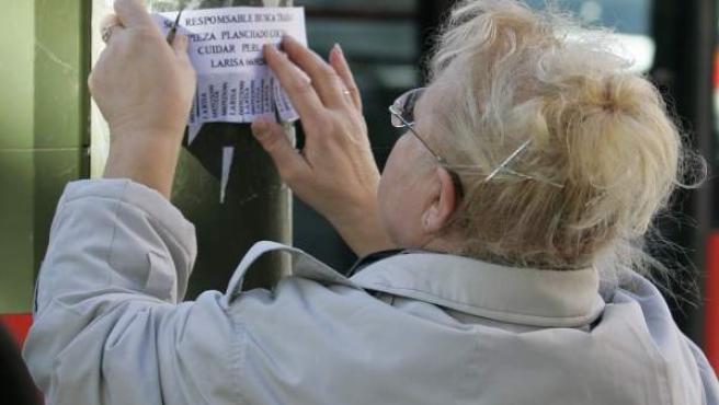 Una mujer coloca un anuncio donde busca trabajo en un poste de un semáforo en Madrid, en una imagen de archivo.