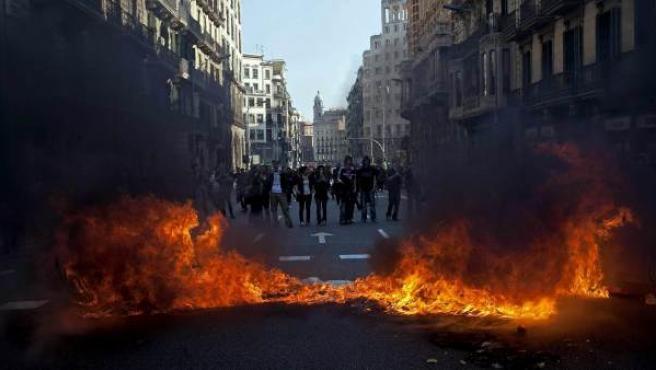 Un coche y diversos contenedores (en la foto) han resultado quemados durante los incidentes registrados en la confluencia de las calles Diputación y Balmes de Barcelona, al final de una manifestación de universitarios contra los recortes del gobierno catalán.