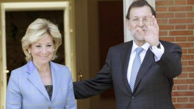 Rajoy saluda a la prensa antes de iniciar su encuentro con Aguirre.