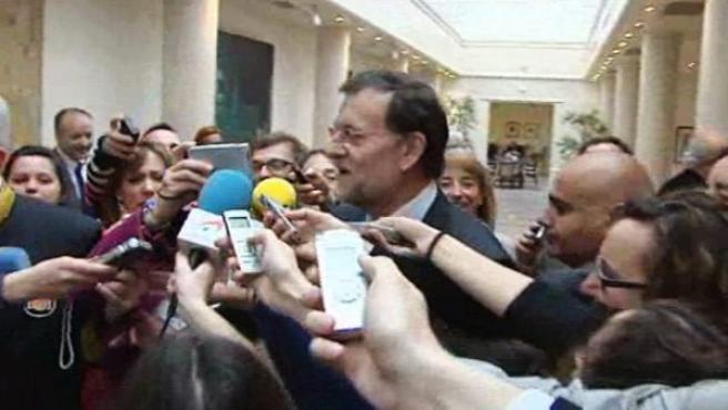 Rajoy tratando de evitar a los periodistas en el Senado.