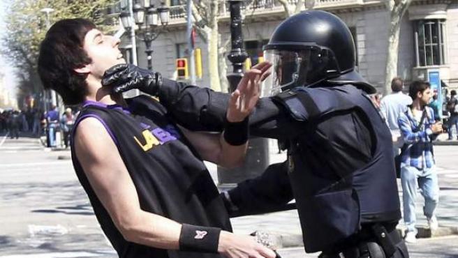 Un mosso d'esquadra detiene a un manifestante en Barcelona durante los disturbios que se han producido en la jornada de huelga general del 29-M convocada por los sindicatos contra la reforma laboral.
